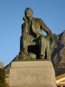 """""""Statue of Cecil John Rhodes at UCT (5829551829)"""" by Ian Barbour from Cape Town, South Africa - Statue of Cecil John Rhodes at UCT. Licensed under Public Domain via Wikimedia Commons - https://commons.wikimedia.org/wiki/File:Statue_of_Cecil_John_Rhodes_at_UCT_(5829551829).jpg#/media/File:Statue_of_Cecil_John_Rhodes_at_UCT_(5829551829).jpg"""